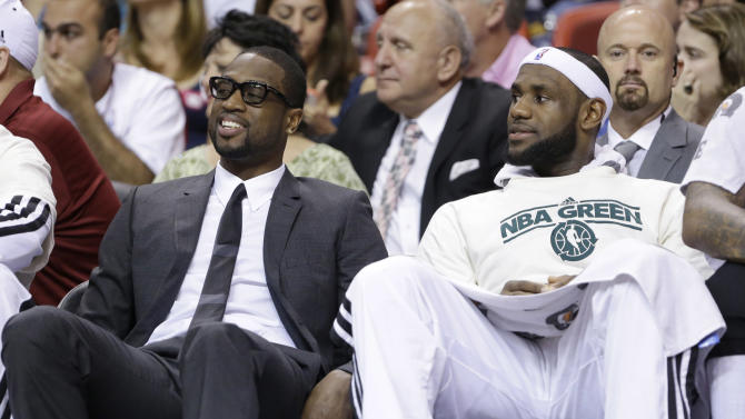 Miami Heat guard Dwyane Wade, left, sits on the bench with forward LeBron James during the first half of an NBA basketball game against the Milwaukee Bucks, Tuesday, April 9, 2013 in Miami. Wade was ruled out of Tuesday's home game against the Bucks, the fifth straight contest that the All-Star guard will miss while tending to a sprained ankle and bruised knee. (AP Photo/Wilfredo Lee)