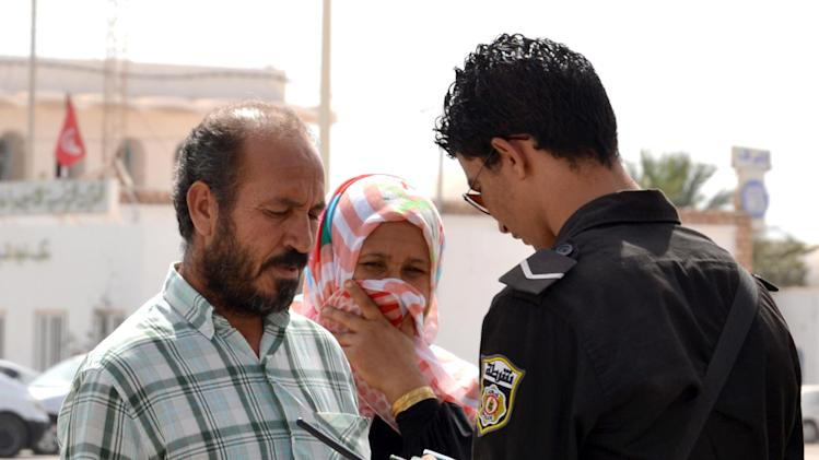 A Tunisian custom officer checks the identifications of a couple fleeing from Libya at the Ras Ajdir border post between Libya and Tunisia, southern Tunisia, Thursday, July 31, 2014. Up to 6,000 people a day have fled Libya into neighboring Tunisia this week, the Tunisian foreign minister said Wednesday, the biggest influx since Libya's 2011 civil war in a sign of the spiraling turmoil as rival militias battle over control of the airport in the capital Tripoli. (AP Photo/Ali Manssour)