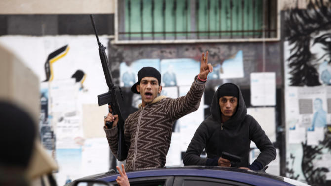 Libyan gunmen pose as they celebrate on a vehicle on the early morning of the second anniversary of the revolution that ousted Moammar Gadhafi, in Benghazi, Libya, Sunday, Feb. 17, 2013.  (AP Photo/Mohammad Hannon)
