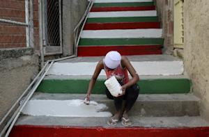 A woman paints stairs with Christmas colors at the…