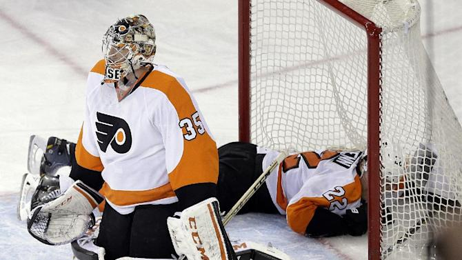 Philadelphia Flyers goalie Steve Mason (35) and teammate Luke Schenn (22) react after New York Rangers' Dominic Moore scored a goal during the third period of an NHL hockey game Wednesday, March 26, 2014, in New York. The Rangers won 3-1