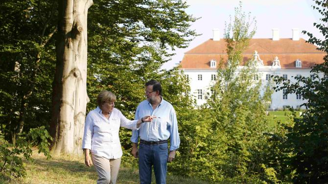 German Chancellor Merkel strolls with Spanish Prime Minister Rajoy near the German government's guesthouse in Meseberg