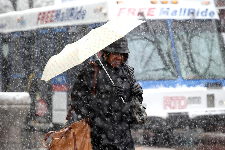 A woman uses an umbrella to ward off heavy snow  in downtown Denver on Wednesday, May 1, 2013. The Denver area could get up to around 5 inches, but not much is sticking to the pavement, still warm after a weekend with temperatures in the 70s. (AP Photo/Ed Andrieski)