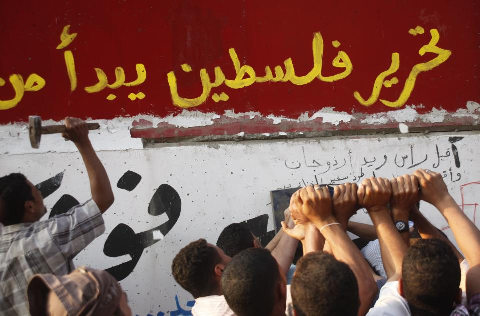 "Egyptian activists demolish a concrete wall built around a building housing the Israeli embassy in Cairo, Egypt, to protect it against demonstrators,  Friday, Sept.9, 2011. Arabic reads "" liberation of Palestine begin from Egypt"" (AP Photo/Amr Nabil)"