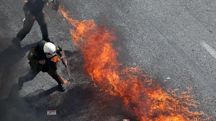 Riot police try to avoid a petrol bomb in Athens, during a 24-hour nationwide general strike on Thursday, Oct. 18, 2012. Greece was facing its second general strike in a month Thursday as workers protested over another batch of austerity measures that are designed to prevent the bankruptcy of the country. (AP Photo/Thanassis Stavrakis)