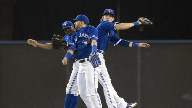 Toronto Blue Jays' Rajai Davis, left, Jose Bautista, center, and Colby Rasmus celebrate their 4-2 win over the Baltimore Orioles after a baseball game in Toronto, Saturday June 22, 2013. (AP Photo/the Canadian Press, Chris Young)