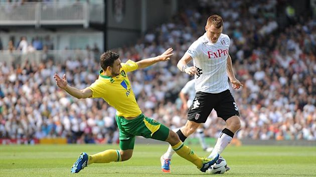 Norwich City's Bradley Johnson (left) and Fulham's John Arne Riise battle for the ball
