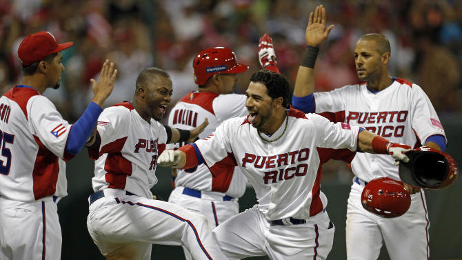 Puerto Rico's Mike Aviles, second from right, celebrates with teammates after hitting a two run home run in the 4th inning of the World Baseball Classic first round game against the Dominican Republic in San Juan, Puerto Rico, Sunday, March 10, 2013. (AP Photo/Andres Leighton)