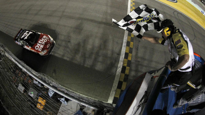 Tony Stewart takes the checkered flag to win the NASCAR Sprint Cup series auto race and clinch the series championship, at Homestead-Miami Speedway in Homestead, Fla., Sunday, Nov. 20, 2011. (AP Photo/Todd Warshaw, Pool)