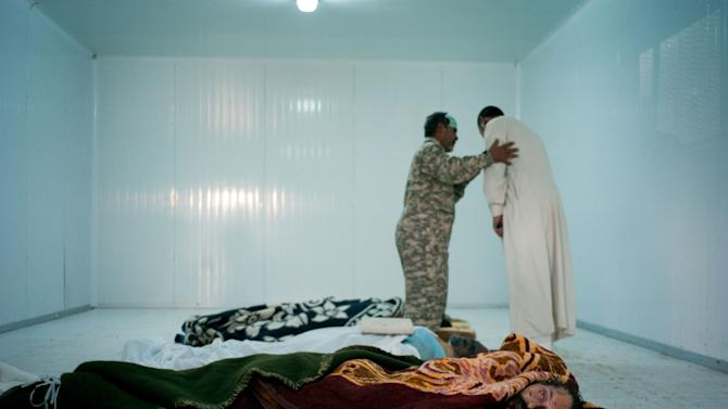 A man reacts while viewing the bodies of Libyan dictator Moammar Gadhafi, background, his ex-defense minister Abu Bakr Younis and his son, Muatassim Gadhafi, foreground, in a commercial freezer at a shopping center in Misrata, Libya, Saturday, Oct. 22, 2011. Libya's new leaders will declare liberation on Sunday, officials said, a move that will start the clock for elections after months of bloodshed that culminated in the death of longtime dictator Moammar Gadhafi. (AP Photo/David Sperry)