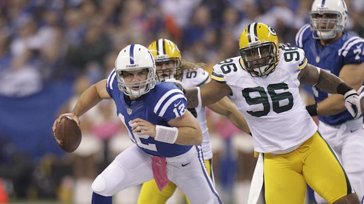 Indianapolis Colts quarterback Andrew Luck runs out of the tackle of Green Bay Packers defensive tackle Mike Neal (96) during the first half of an NFL football game in Indianapolis, Sunday, Oct. 7, 2012. (AP Photo/Michael Conroy)