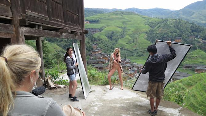 This Sept. 10, 2012 image released by Sports Illustrated shows a model being photographed on location in Guilin, China, for the 2013 Sports Illustrated Swimsuit issue. Sports Illustrated took its models to all seven continents for the first time. The around-the-globe effort will be chronicled by the Travel Channel in a special on Feb. 17. Sports Illustrated said Tuesday it's the first to do a fashion shoot in Antarctica, where temperatures were subfreezing.  Among the locations featured are Namibia, China, Australia and Easter Island, one of the most remote places on Earth. Swimsuit magazine editor MJ Day says it took seven months to complete. Sports Illustrated will reveal its cover Monday. It can be a star-making opportunity. Last year's cover model was Kate Upton. The magazine hits newsstands Feb. 12. (AP Photo/Valery Gherman for Sports Illustrated) FOR NORTH AMERICAN USE ONLY IN CONJUNCTION WITH THE PROMOTION OF THE TRAVEL CHANNEL SPECIAL UNTIL FEB. 28, 2013.