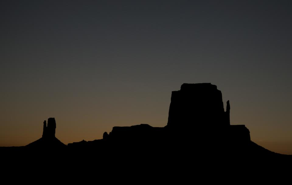 "West Mitten, left,  and East Mitten buttes are silhouetted against the last light from the setting sun after the Ring of Fire eclipse, Sunday, May 20, 2012, in Monument Valley, Ariz.   The western United States watched as a rare ""ring of fire"" eclipse crossed their skies.  (AP Photo/Julie Jacobson)"