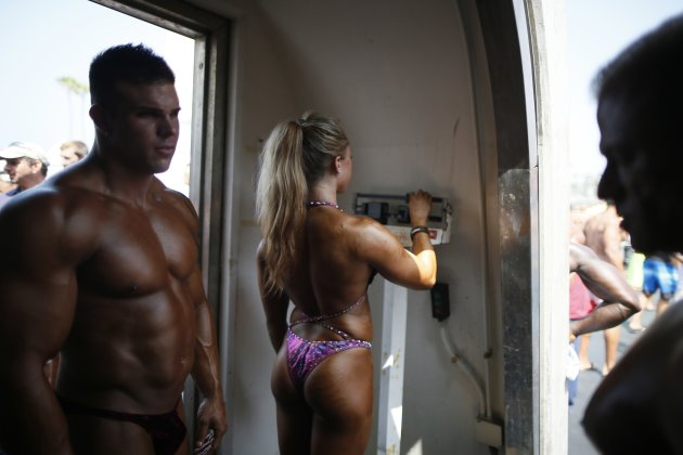 A woman weighs herself before the Muscle Beach Independence Day bodybuilding contest on Venice Beach in Los Angeles, California