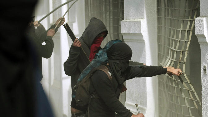 Protesters try to break a shop's gate after a May Day march in Santiago, Chile, Tuesday, May 1, 2012. Clashes with security forces and riots marred the rally that marks International Labor Day. (AP Photo/Luis Hidalgo)