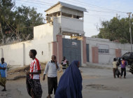 Residents walk outside of the Medecins Sans Frontieres (Doctors without Borders) compound in Mogadishu, Somalia Thursday, Dec. 29, 2011. A disgruntled former employee shot at least two international workers from the aid group Doctors Without Borders at the group's office in the Somali capital, a security guard said Thursday. (AP Photo/Mohamed Sheikh Nor)