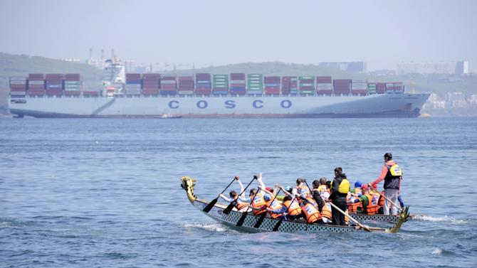 Athletes compete in a Dragon boat pulling race in the Sea of Japan waters, with the COSCO Yantian cargo ship seen in the background, near the far eastern port of Vladivostok