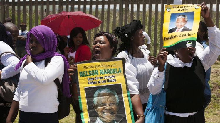A crowd sings and cheers at the gate of the airport in Mthatha, a day before the arrival of the body of late former South African President Mandela