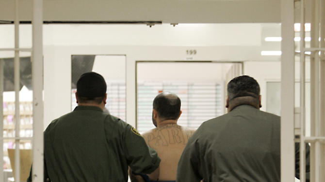 FILE - In this Jan. 14, 2009 file photo, an inmate on suicide watch is escorted by correctional officers at the California Substance Abuse Treatment Facility in Corcoran, Calif. Gov. Jerry Brown is criticizing attorneys representing inmates and court-appointed masters and experts who he says have a financial incentive to drag out lawsuits against the state.  One of the lawsuits involves inmates' mental health care including suicide prevention efforts. (AP Photo/Rich Pedroncelli, File)