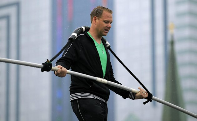 FILE - In this May 16, 2012 photo, Nik Wallenda performs a walk on a tightrope in the rain during training for his walk over Niagara Falls in Niagara Falls, N.Y. For his latest feat, the professional daredevil is going to try to do an unharnessed tightrope walk high above the beach in Atlantic City, N.J. Atlantic City tourism officials are hoping 50,000 or more people show up to watch Thursday, Aug. 9, 2012, as Wallenda attempts to traverse a line connecting the Atlantic Club Casino Hotel to the Tropicana Casino & Resort. (AP Photo/David Duprey, File)