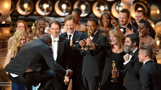 "Director Steve McQueen, left, celebrates with the cast and crew of ""12 Years a Slave"" as they accept the award for best picture during the Oscars at the Dolby Theatre on Sunday, March 2, 2014, in Los Angeles. (Photo by John Shearer/Invision/AP)"