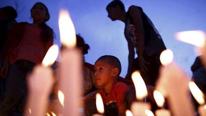 A boy sit next to the lit candles as he takes part in a candle light vigil, a month after the April 25 earthquake in Kathmandu