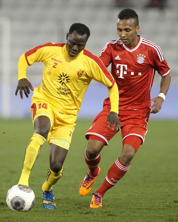 Bayern Munich's Julian Green, right, of Munich and Balla Jabir of Al-Merrikh, challenge for the ball,  during their friendly soccer match, at Al-Saad stadium in Doha Thursday, Jan. 9, 2014