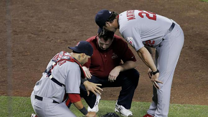 St. Louis Cardinals catcher Yadier Molina, left, has his hand checked by the team trainer and manager Mike Matheny during the ninth inning of a baseball game against the Arizona Diamondbacks Tuesday, May 8, 2012, in Phoenix. Molina left the game.  (AP Photo/Matt York)
