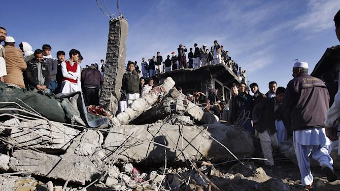 Local residents stand over the rubble of a damaged market caused by Saturday's bombing in Quetta, Pakistan on Sunday, Feb. 17, 2013. The death toll from the horrific bombing that tore through the crowded vegetable market in a mostly Shiite Muslim neighborhood of southwestern Pakistan climbed to 81 with many of the severely wounded dying overnight, a Pakistani police official said Sunday. (AP Photo/Arshad Butt)