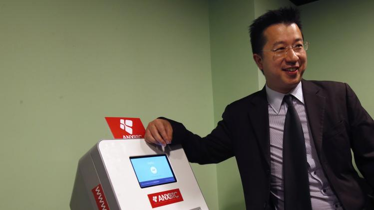 ANXBTC bitcoin exchange Chief Executive Lo poses with Hong Kong's first bitcoin ATM during a demonstration in Hong Kong