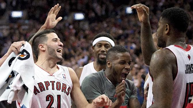 Toronto Raptors' Amir Johnson, right, who made the game winning shot, is congratulated by teammates Greivis Vasquez, left, and Dwight Buycks after defeating the Boston Celtics in NBA action in Toronto on Friday March 28, 2014. The Raptors clinched a playoff spot with the win