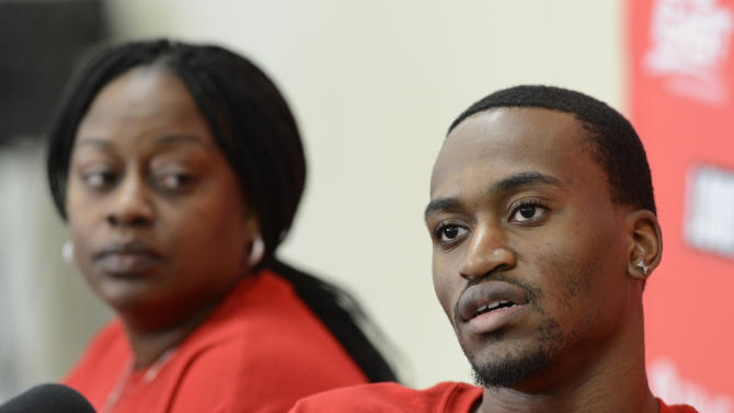 Louisville basketball player  Kevin Ware, right, answers questions ss his mother, Lisa Junior, looks on during an interview Wednesday April 3, 2013, at the KFC Yum! Center practice facility in Louisville, Ky. Ware was released from an Indianapolis hospital Tuesday, two days after millions watched him break his right leg on a horrifying play trying to block a shot during an NCAA college basketball regional championship game against Duke.  (AP Photo/Timothy D. Easley)