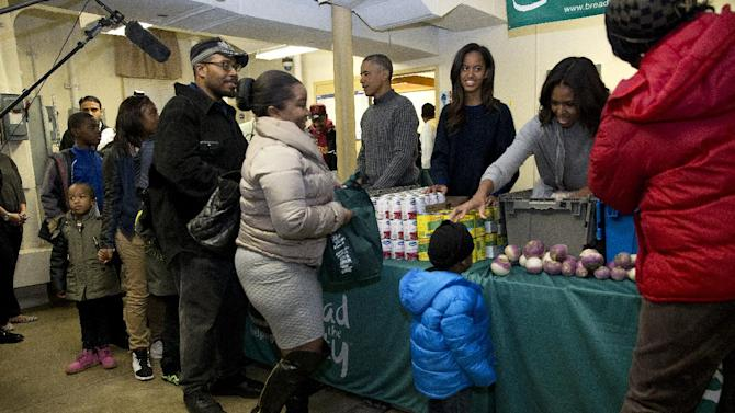 "President Barack Obama, back left, with daughter Malia and first lady Michelle Obama, greet people as they distribute food at ""Bread for the City""  Wednesday, Nov. 26, 2014, in Washington, as part of  Thanksgiving tradition of participation in a service event. (AP Photo/Jacquelyn Martin)"