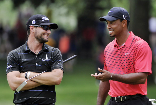 Kyle Stanley, left, and Tiger Woods talk on the 11th hole during the final round of the Bridgestone Invitational golf tournament at Firestone Country Club in Akron, Ohio, Sunday, Aug. 5, 2012. (AP Photo/Phil Long)