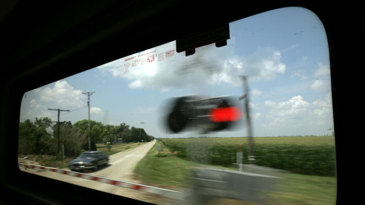 FILE - In this July 9, 2007, file photo Amtrak's Lincoln Service train passes Illinois cornfields as it speeds through a crossing en route to Chicago. The two biggest players in the nation's pursuit of high-speed rail said Thursday, Jan. 17, 2013, they'll work together to search for trains that will operate at up to 220 miles per hour along both coasts of the United States. (AP Photo/Jeff Roberson, File)