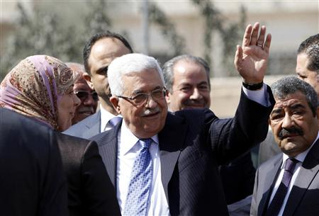 Palestinian President Abbas waves as he arrives at a polling station in Al-Bireh