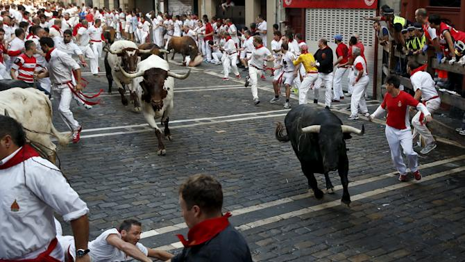 A runner falls next to a Jandilla fighting bull as another Jandilla bull charges at a runner at the Mercaderes curve during the first running of the bulls of the San Fermin festival in Pamplona