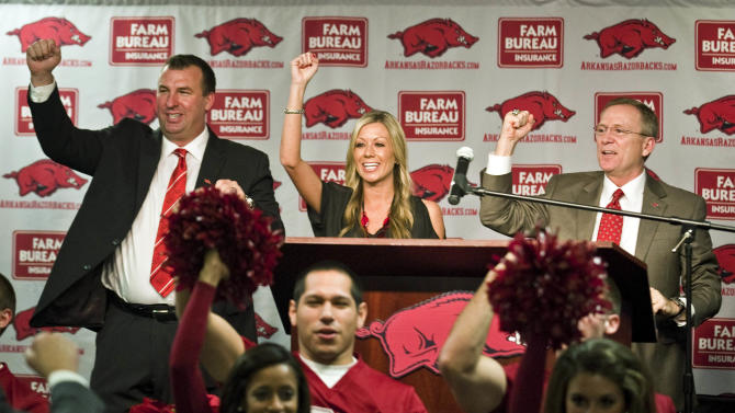 New Arkansas head coach Bret Bielema, left, his wife, Jen, center, and athletic director Jeff Long, right, Call the Hogs during an NCAA college football news conference in Fayetteville, Ark., Wednesday, Dec. 5, 2012. Bielema, who will be paid $3.2 million annually for six years, replaces interim coach John L. Smith, who was hired after Bobby Petrino was fired in April. (AP Photo/April L. Brown)
