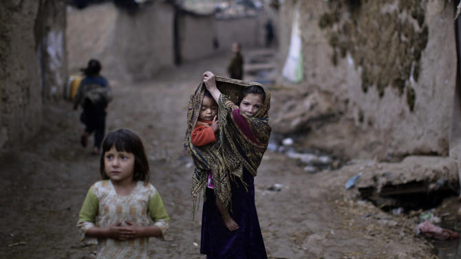 An Afghan refugee girl, center, uses her head scarf to cover her sleeping sister, while walking in an alley of a poor neighborhood on the outskirts of Islamabad, Pakistan, Tuesday, April 9, 2013. Pakistan hosts over 1.6 million registered Afghans, the largest and most protracted refugee population in the world, according to the U.N. refugee agency. (AP Photo/Muhammed Muheisen)