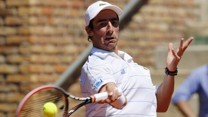 Uruguay's Pablo Cuevas returns the ball to Colombia's Alejandro Gonzalez during their Davis Cup tennis match in Montevideo