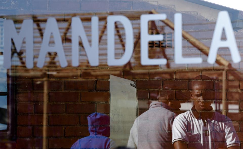 People are reflected in a window of the house of former South African President Nelson Mandela in Soweto, Friday, June 28, 2013. Members of Nelson Mandela's family as well as South African Cabinet ministers have visited the hospital where the 94-year-old former president is critically ill. (AP Photo/Markus Schreiber)