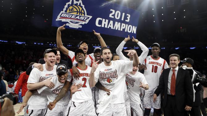 Louisville's Russ Smith (2), Gorgui Dieng (10) and Luke Hancock, center, celebrate with the team after their 78-61 win over Syracuse in an NCAA college basketball championship game at the Big East Conference tournament, Saturday, March 16, 2013, in New York. (AP Photo/Frank Franklin II)