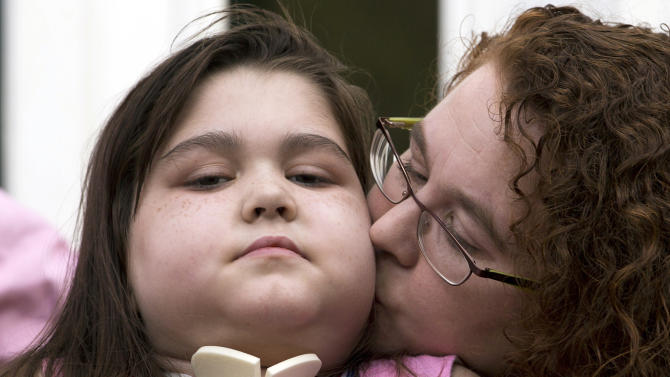 Lung transplant recipient Sarah Murnaghan, receives a kiss from her mother Janet, during a news conference after arriving home from the hospital Tuesday, Aug. 27, 2013, in Newtown Square, Pa. Sarah Murnaghan, who has end-stage cystic fibrosis, received two lung transplants this summer at the Children's Hospital of Philadelphia after a federal judge intervened in her parents' lawsuit challenging national transplant rules that put her at the end of the waiting list for adult lungs. (AP Photo/Matt Rourke)