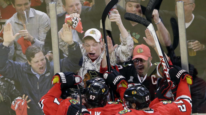 Chicago Blackhawks' Marcus Kruger (16), left, celebrates with teammates after scoring a goal during the third period of Game 1 of an NHL hockey playoffs Western Conference semifinal against the Detroit Red Wings in Chicago, Wednesday, May 15, 2013. (AP Photo/Nam Y. Huh)