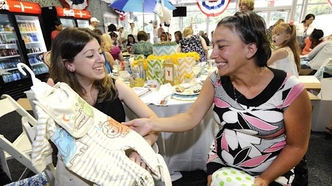 Kim Antal of Albany, N.Y., left, and Jennifer Lyman of Ballston Spa, N.Y. admire the baby shower gifts they received at Operation Shower, hosted by Melissa Joan Hart and sponsored by Carousel Designs at The 2012 Barclays, on Wednesday, Aug. 22, 2012 in Farmingdale, NY. Antal's husband, Troy Antal is a Sgt. 1st Class in the National Guard and Lyman, a former Army Specialist, is married to Jesse Lyman who is a Specialist in the Army. (Photo by Kathy Kmonicek/Invision for Carousel Designs/AP Images)