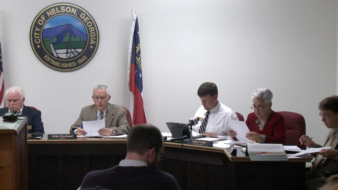 """In a this image made from video, the Nelson, Ga. City Council meets to vote on a mandatory gun ownership ordinance for all heads-of-household, Monday, April 1, 2013. From left are council member Jackie Jarrett, Mayor Mike Haviland, council member Duane Cronic, council member Edith Portillo, and city attorney Jeff Rusbridge. Council members in Nelson, a city of about 1,300 residents that's located 50 miles north of Atlanta, voted unanimously to approve the Family Protection Ordinance. The measure requires every head of household to own a gun and ammunition to """"provide for the emergency management of the city"""" and to """"provide for and protect the safety, security and general welfare of the city and its inhabitants."""" (AP Photo/Johnny Clark)"""