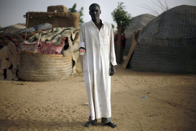 Issa Alzouma, 39, poses in front of his home in Gao, Northern Mali, Thursday Jan. 31, 2013. Alzouma's arm was amputated by Islamist radicals on Dec. 21, 2012, after being charged by the Islamic tribunal of spying. Alzouma, a father of three, denied the charges, and said he was just changing the faulty plug on his motorcycle's engine alongside the road. Islamist extremists fled the city Saturday as French, Chadian and Nigerien troops arrived, ending 10 month of radical Islamic control over the city.(AP Photo/Jerome Delay)