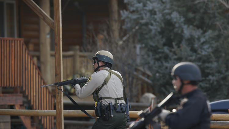 "San Bernardino County sheriff's deputies conduct door-to-door search in Big Bear, Calif, Thursday, Feb. 7, 2013.  Thousands of police officers hunted Thursday for one of their own: a former Los Angeles officer angry over his firing and sought in a deadly shooting rampage after warning he would wage ""warfare"" on those who wronged him, authorities said. (AP Photo/Jae C. Hong)"