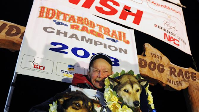 Mitch Seavey became the oldest winner and a two-time Iditarod champion when he drove his dog team under the burled arch in Nome on Tuesday evening, March 12, 2013. He sits with his two lead dogs, Tanner, left and Taurus, right. (AP Photo/The Anchorage Daily News, Bill Roth)  LOCAL TV OUT (KTUU-TV, KTVA-TV) LOCAL PRINT OUT (THE ANCHORAGE PRESS, THE ALASKA DISPATCH)