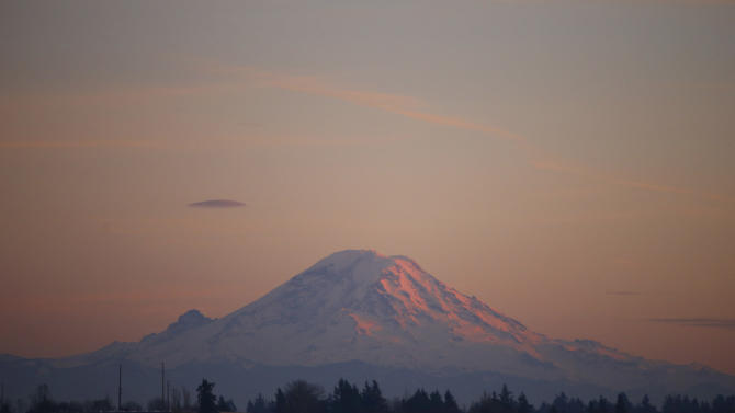 Mount Rainier is pictured as the last rays of sunlight hit its western side, taken from the tarmac of Seattle Airport